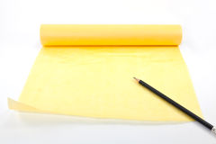 Yellow paper scroll with black pencil Royalty Free Stock Photography