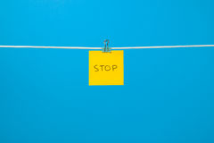 """Yellow paper sheet on the string with text """"Stop"""" Royalty Free Stock Photo"""