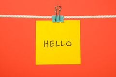 "Yellow paper sheet on the string with text ""Hello"" Royalty Free Stock Photo"