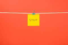 "Yellow paper sheet on the string with text ""Stop"" Royalty Free Stock Photos"