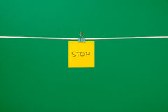 "Yellow paper sheet on the string with text ""Stop"" Stock Images"