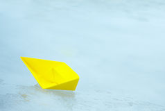 Yellow paper ship in a puddle Royalty Free Stock Images
