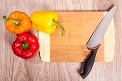 Yellow paprika on cutting board whit knife. Red pepper strips and knife whit wood background. Stock Photos