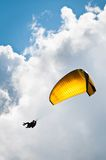 Yellow parachute against sky and clouds Stock Images