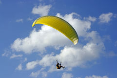 Yellow paraglide. Flying yellow paraglide on the blue sky stock photo