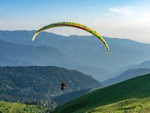Yellow paraglider in blue clear sky over the Green Mountain stock images