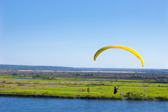 Yellow Paraglider in blue sky above the river and riverside. Bird`s eye panorama. Tom river. Tomsk city, Russia Stock Image
