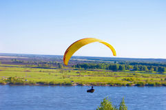 Yellow Paraglider in blue sky above the river and riverside. Bird`s eye panorama. Tom river. Tomsk city, Russia. Yellow bright Paraglider in blue sky above the Royalty Free Stock Images
