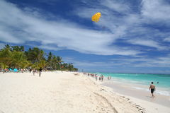 Yellow Paraglider hangs over sunbathers on white Caribbean beach Royalty Free Stock Photos