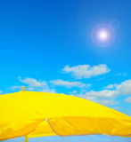 Yellow parasol on the beach under a clear sky Royalty Free Stock Photography