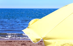 Yellow parasol on the shore of the ocean in the hot summer sunny Royalty Free Stock Photography