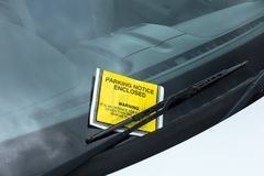 Yellow parking enforcement ticket stuck to car windscreen stock images