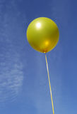 Yellow party balloon on blue sky Royalty Free Stock Photos