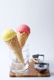 Yellow passion fruit and red strawberry ice cream cones Stock Image