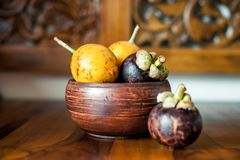 Yellow passion fruits and mangosteen in wooden bowl. One mangosteen lying near bowl. Mix of exotic fresh fruits from Bali, Asia. Yellow passion fruits and Stock Images