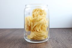 Yellow pasta in a can on wooden table stock image