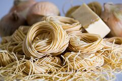 Yellow Pasta Beside Onions Royalty Free Stock Photography