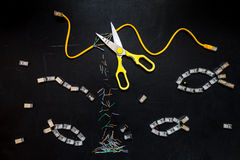 Yellow patch cord cut by scissors and connectors RJ45 , composition isolated over the black chalkboard background. Royalty Free Stock Image