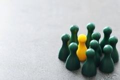 Yellow pawn among green ones on gray table. Stock Photo