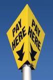 Yellow pay here car parking sign. stock photos