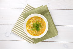 Yellow pea soup in bowl on white wooden background Royalty Free Stock Photo