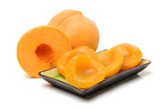 Yellow peach and Canned peach halves in bowl. Isolated on a white background stock image