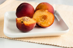 Yellow peaches on white square plate Royalty Free Stock Photo