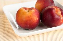 Yellow peaches on white square plate Royalty Free Stock Photo