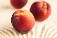 Yellow peaches on yellow placemat Royalty Free Stock Photo