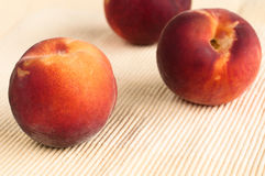 Yellow peaches on yellow placemat Royalty Free Stock Images