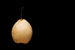 Yellow pear on black background Royalty Free Stock Photos