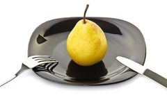 Yellow pear on a black plate with fork and knife Stock Photos
