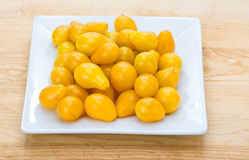 Yellow pear cherry tomatoes on white plate Royalty Free Stock Photos