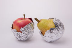 Yellow pear and red apple wrapped in foil on a white background Royalty Free Stock Images