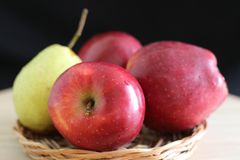 Yellow pear and red apples. On straw plate stock photo