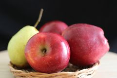 Yellow pear and red apples. On straw plate royalty free stock photos