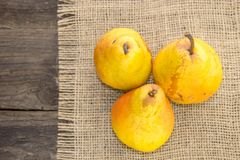 Yellow pear on a rustic background. Delicious, juicy, ripe, yellow pear on a rustic background on a wooden table Stock Image