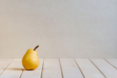 Yellow pear on the white table Stock Images