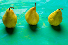 Yellow pears on colorful turquoise background. Stock Images