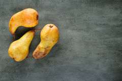 Yellow pears on dark stone background, top view. Royalty Free Stock Images