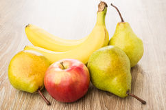 Yellow pears, red apple and bananas on table Stock Photography