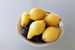 Yellow pears in round plaet. Big yellow pears and plums in white round table centered on white glass table topview Stock Image
