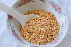 Yellow peas in a bowl with white spoon. Photo of yellow peas in a bowl with white spoon Royalty Free Stock Photo