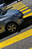Yellow pedestrian crossing on black pavement Stock Photo