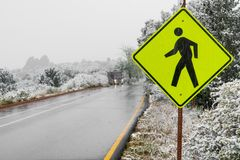 Yellow pedestrian crosswalk crossing street sign in winter snow royalty free stock photography