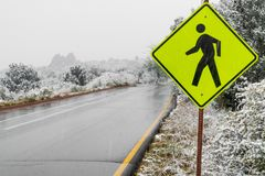 Yellow pedestrian crosswalk crossing street sign in winter snow stock images