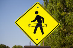 A yellow pedestrian crosswalk sign with a hula hoop drawn onto it. Royalty Free Stock Photography