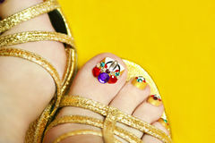 Yellow pedicure. Art coverage with crystals on the nail women's feet in sandals on a yellow background royalty free stock photos