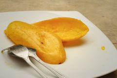 Yellow peel mango with fork on white plate. Royalty Free Stock Photography