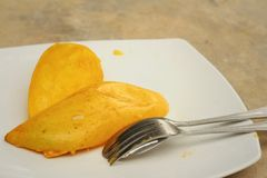 Yellow peel mango with fork on white plate. Royalty Free Stock Photos